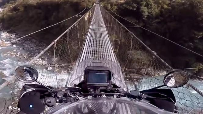 Przejazd motocyklem po moście linowym w Himalajach